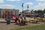 Citizens enjoying a picnic on a picnic table next to a playground in a city park