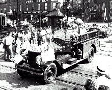 A black and white image of a fire truck driving through a town with many spectators watching nearby